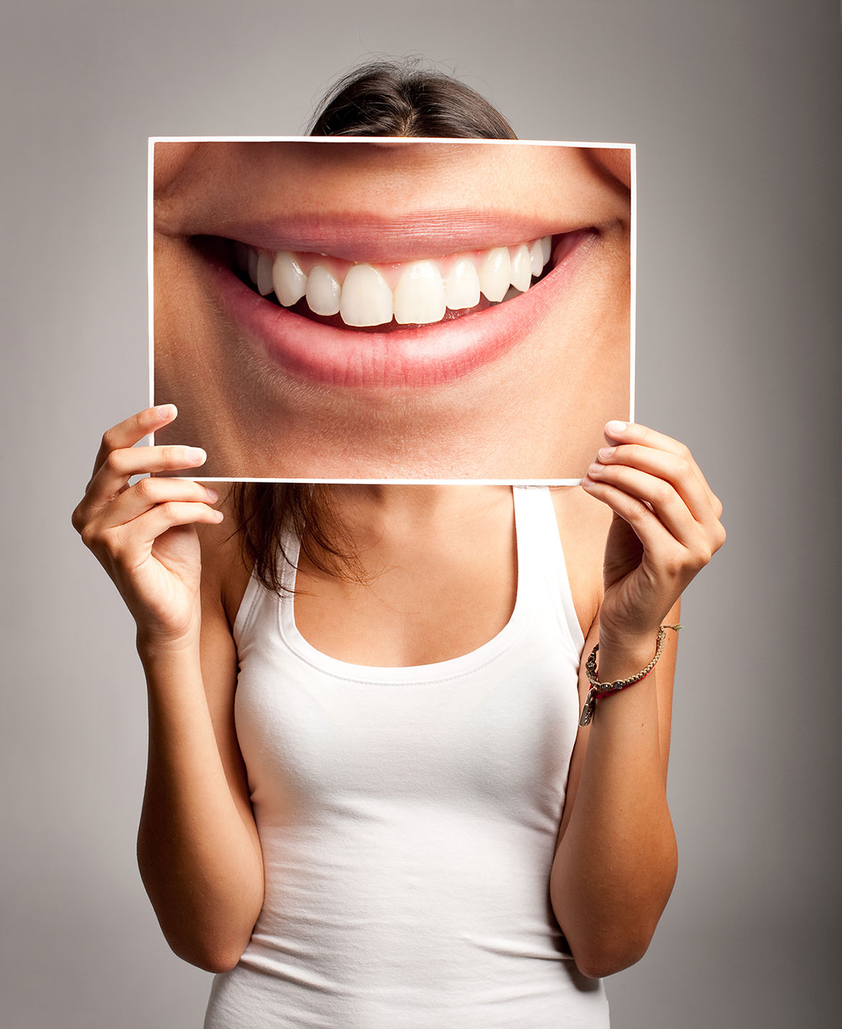Woman Holds A Beautifully Enlarged Photo Of Her Smile Over Her Face