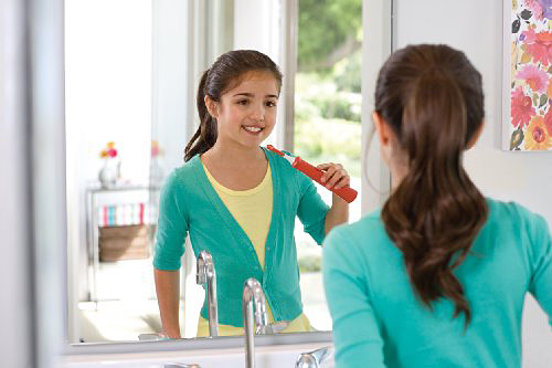 Teenage Girl Brushing Teeth With Electric Tooth Brush