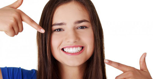 Teenage Girl Pointing At Her Beautiful Teeth