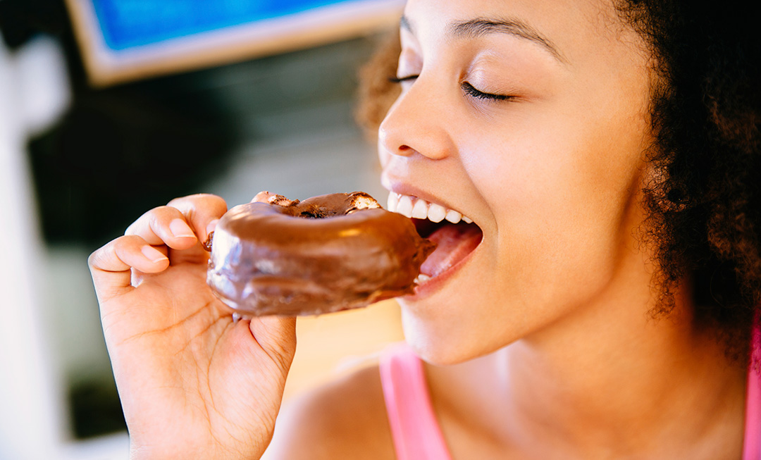 Girl Eating a Donut - Preventive Dentistry Helps Prevent Cavities