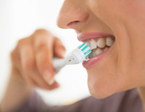 Teen Brushing Teeth With Electric Toothbrush