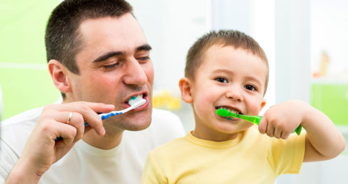 Father and Son Having Fun Brushing Teeth