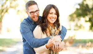 Smiling Man Hugs Happy Woman in Courtyard