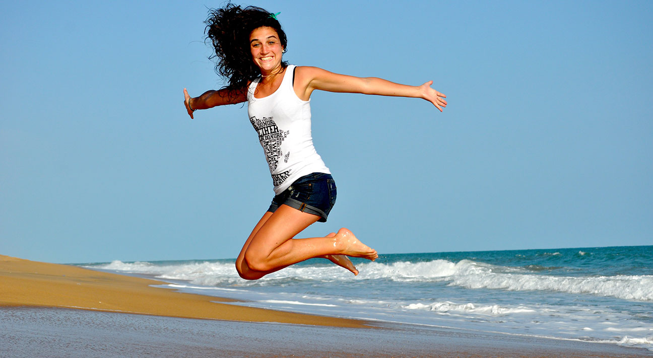 Smiling Woman Jumps For Joy On Beach