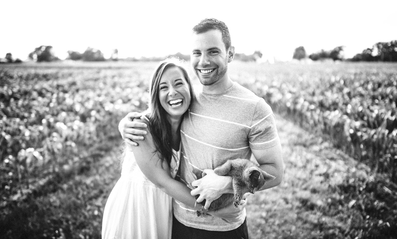 Smiling Woman and Man in Vineyard with Cat