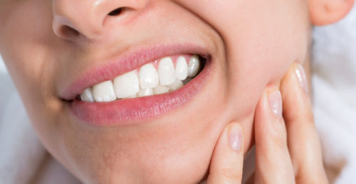 Combat Sensitive Teeth See Your Dentist - Woman Holding Sore Jaw